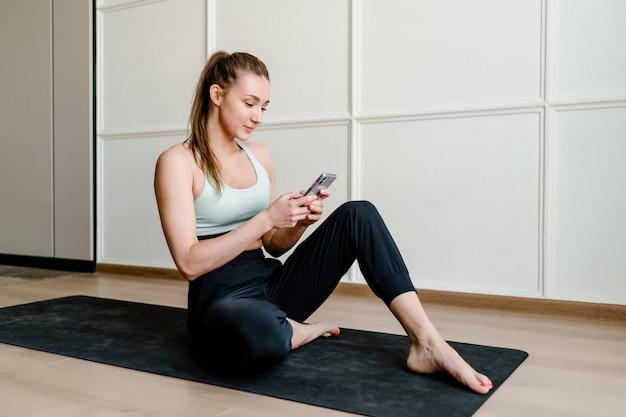 Sportieve vrouwenzitting op yogamat thuis met online telefoon