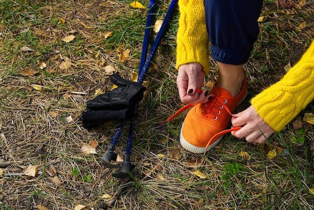 Sportieve wandelende vrouw die schoenveters aan haar joggingschoenen koppelt terwijl ze een pauze neemt na een wandeling in de herfstbos. wandelen concept, gezonde levensstijl buitenshuis