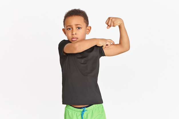 Sportieve zelfverzekerde afrikaanse jongen in sportkleding die biceps aanspant, kracht en fysiek uithoudingsvermogen aantoont. leuk atletisch kind met een donkere huid dat trots is op zichzelf en pronkt met zijn gespannen armspieren