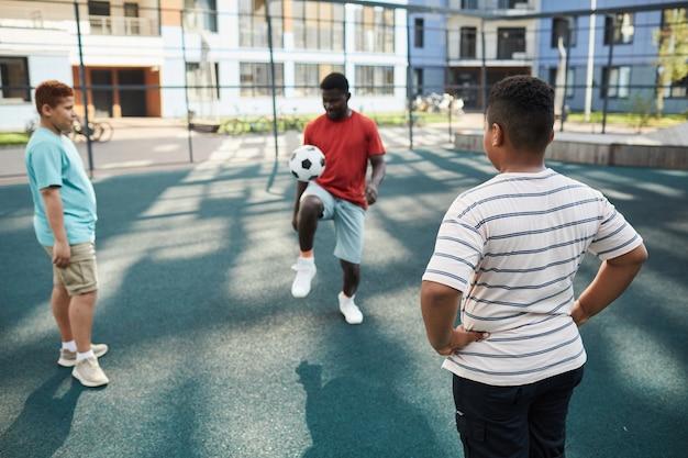Sportieve zwarte vader die voetbal bij de knie schopt tijdens het spelen met zonen op de grond in het appartementencomplex