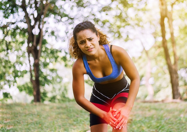 Sportieve zwarte vrouw die op haar knie lijdt, atletenwijfje die pijn op knie hebben