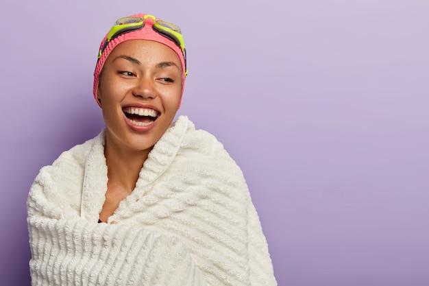 Sportieve zweminstructeur lacht vrolijk, gewikkeld in witte handdoek, geeft les aan stagiair, heeft een perfect gebit, gezonde huid, actieve levensstijl, oefeningen in binnenzwembad. zwemmer meisje met bril