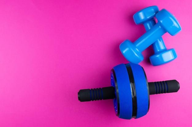 Sportkit: halters, roller voor pers op een roze achtergrond, fotobanner, bovenaanzicht, ruimte voor tekst.