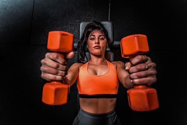 Sportkleding vrouw halter opheffen in de sportschool