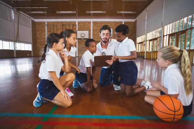 Sportleraar en schoolkinderen bespreken op klembord in basketbalveld