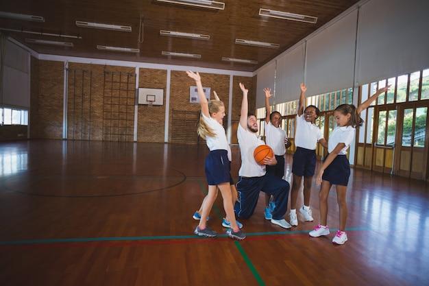 Sportleraar en schoolkinderen spelen in basketbalveld