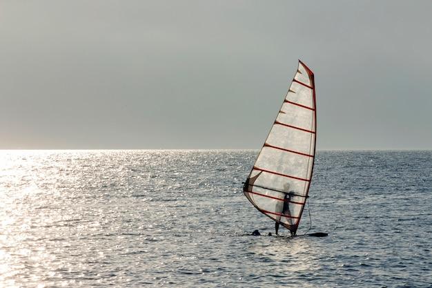 Sportman beoefenen windsurfen bij zonsondergang
