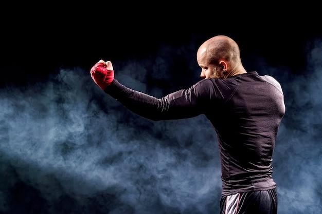 Sportman bokser vechten op zwarte muur met rook