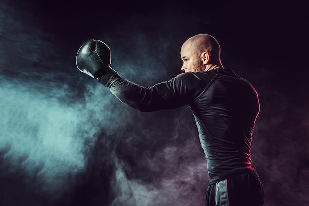 Sportman bokser vechten, uppercut raken op zwarte ruimte met rook
