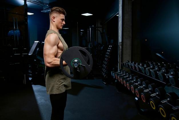 Sportman bouwen biceps met barbell.