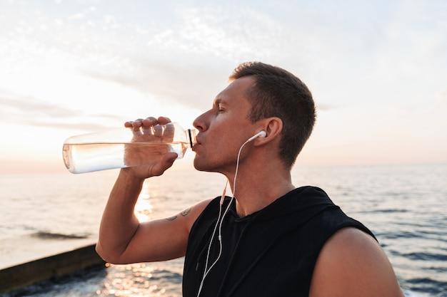 Sportman buiten op het strand luisteren muziek met oortelefoons drinkwater.