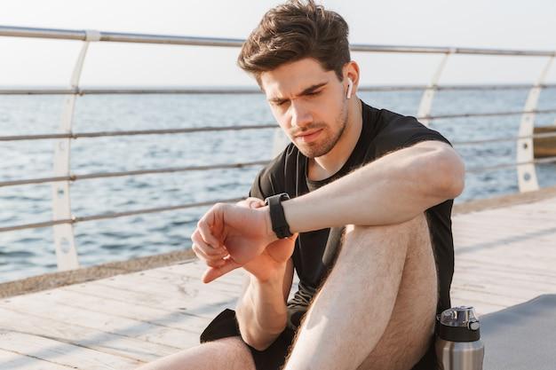 Sportman die buiten horloge kijkt.