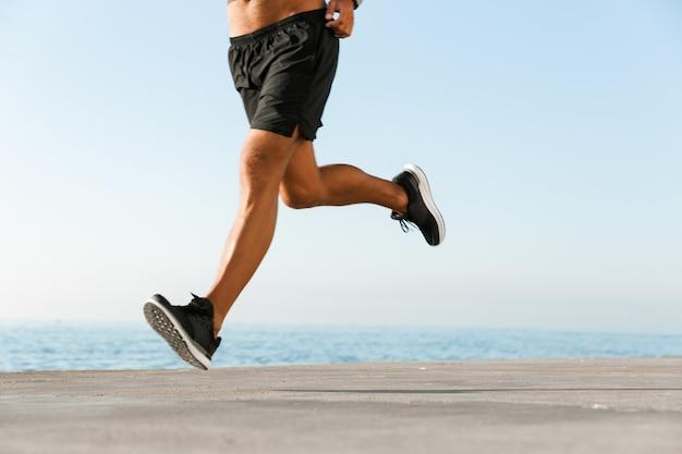 Sportman die buiten op het strand loopt.