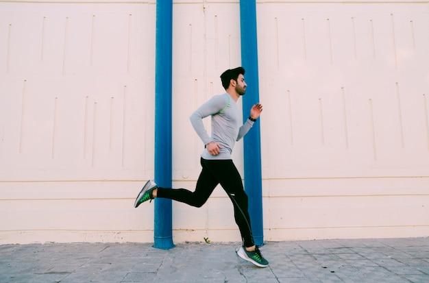 Sportman die dichtbij muur loopt