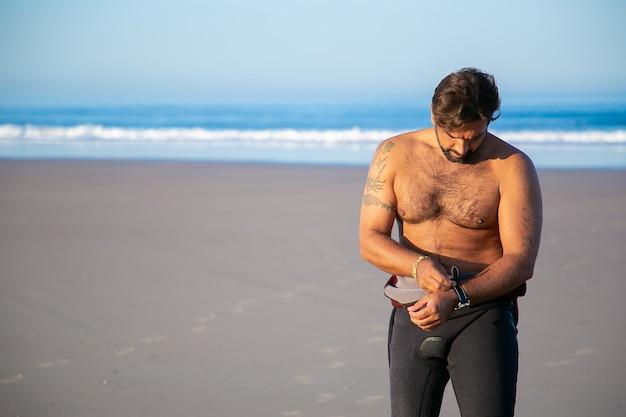 Sportman die een wetsuit aantrekt om op het strand van de oceaan te surfen en de wacht opstijgt