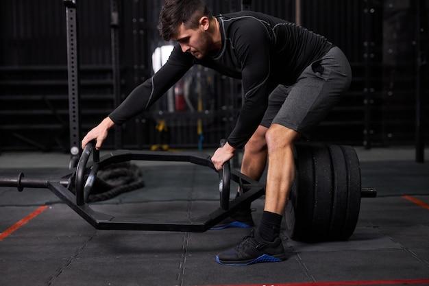 Sportman die gewichten of dwarsbalk op sportschool verplaatst, van uitrusting verandert, houdt barbell vast, jonge man gaat naar oefeningen met sportuitrusting, training