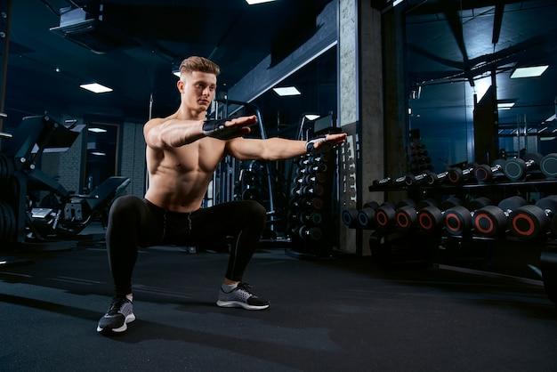 Sportman die hurkzit in gymnastiek doen.