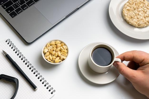 Sportman die knapperige rijstrondes met pinda's, kop van koffie eten dichtbij laptop