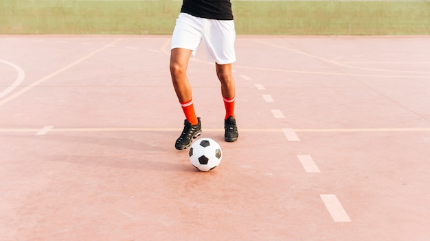 Sportman die met voetbal bij sportgrond spelen