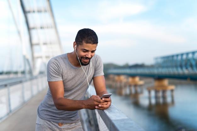 Sportman die mobiele telefoon gebruikt tijdens het trainen en berekent de afstand die hij heeft gelopen