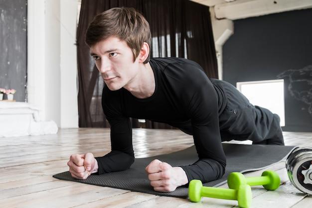 Sportman die plankoefeningen op mat doet