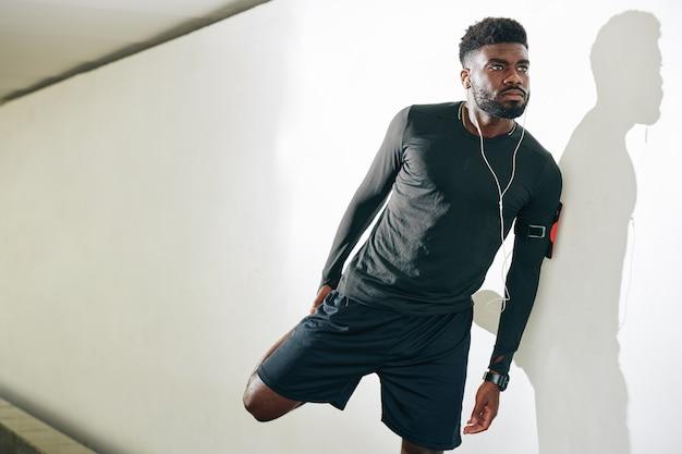 Sportman die quadriceps uitrekt