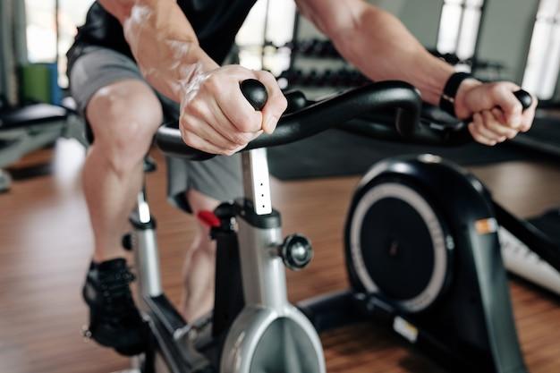 Sportman die stationaire fiets berijdt