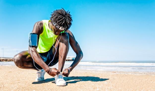 Sportman die zijn schoenveters op het strand knoopt