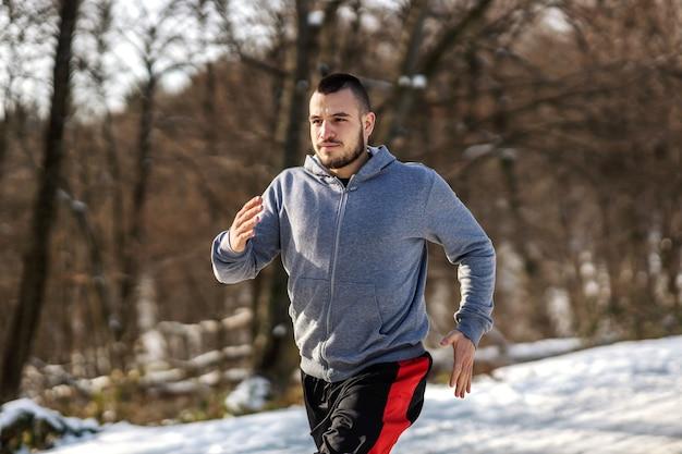 Sportman draait op besneeuwde pad in de natuur op zonnige winterdag. winterfitness, cardio-oefeningen, gezonde gewoonten
