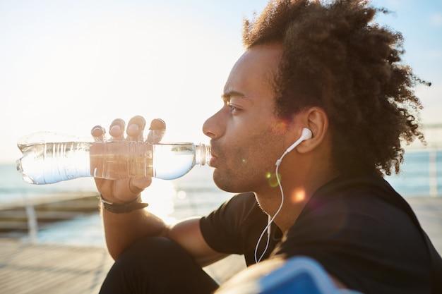 Sportman drinkwater uit fles in ochtendzonlicht