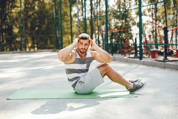 Sportman in een park van de ochtendzomer
