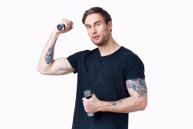 Sportman in een zwarte t-shirt met halters in zijn handen fitnessoefeningen