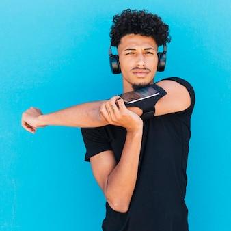 Sportman in hoofdtelefoons en armband uitrekken