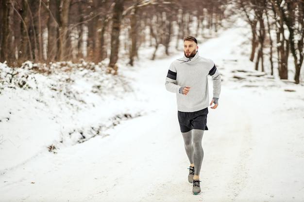 Sportman joggen in de natuur op sneeuw in de winter. gezonde levensstijl, winterfitness, koud weer