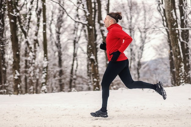 Sportman joggen in het bos op besneeuwde winterdag. gezonde levensstijl, winterfitness