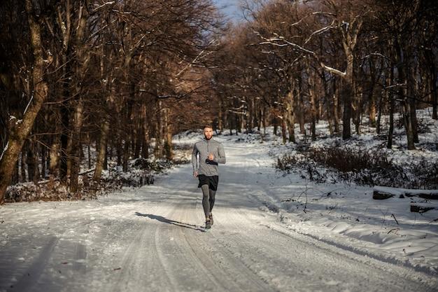 Sportman loopt in de natuur op sneeuw in de winter
