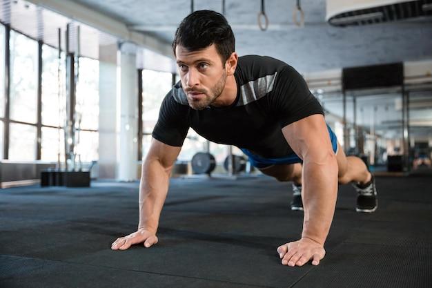 Sportman met blauwe korte broek en zwart t-shirt die push-ups doet