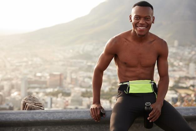 Sportman met blije gezichtsuitdrukking, toont witte perfecte tanden, draagt een legging, houdt fles met water vast, tevreden met goede resultaten, heeft een gespierde lichaamsvorm, is dorstig en uitgedroogd