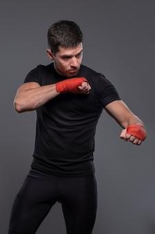 Sportman met boksbandages op handen die defensieve technieken uitwerken