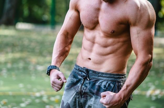 Sportman met naakte torso handhaving van een gezonde levensstijl staande buiten pompen spieren