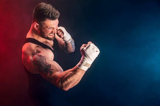 Sportman muay thai bokser vechten op zwarte muur met rook. sport concept.