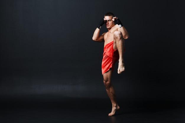 Sportman muay thai man bokser houding advertentie knie schop op zwarte achtergrond