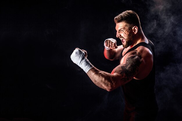 Sportman muay thaise bokser die op zwarte muur met rook vechten.