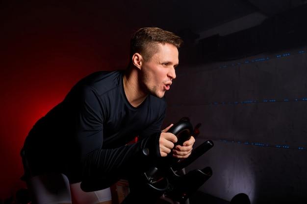 Sportman rijdt ijverig op een hometrainer in de sportschool, de man traint op een hometrainer