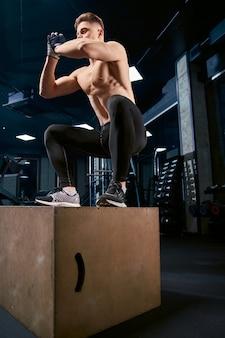 Sportman springen op houten kist.