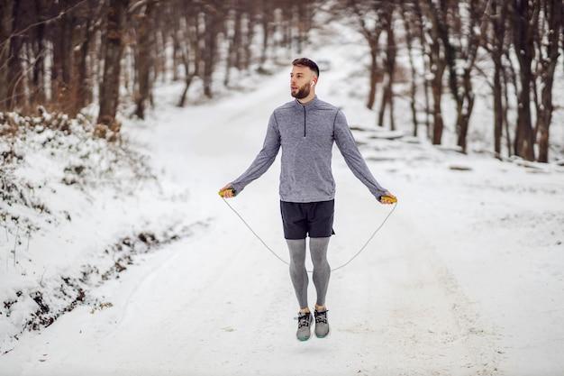 Sportman springtouw op sneeuw in de winter in het bos.