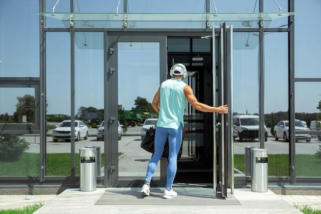 Sportman tegen modern glazen gebouw