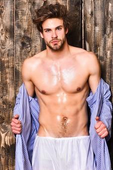 Sportman toont zes pack sexy torso. bachelor sexy lichaam borst en buik. guy glinsterende huid uitkleden badjas. man atleet met fit torso. sexy aantrekkelijke macho warrige haren op houten achtergrond.
