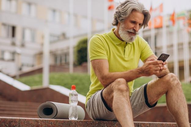 Sportman van middelbare leeftijd zittend op trappen met behulp van telefoon