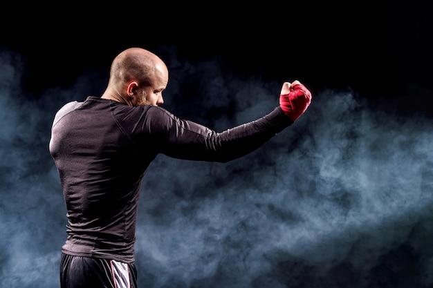 Sportmanbokser het vechten op zwarte muur met rook